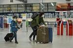 Žena s dítětem v rouškách na letišti