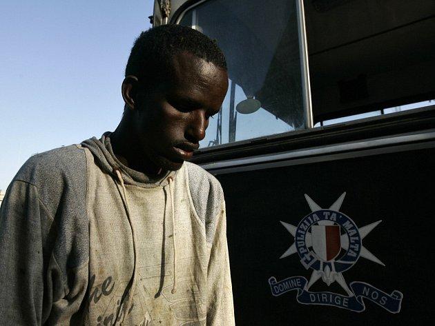 Jeden ze zadržených afrických imigrantů přichází na Maltě k policejnímu autobusu.