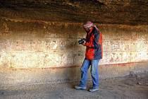 Archeolog pořizuje snímky jeskyní malby