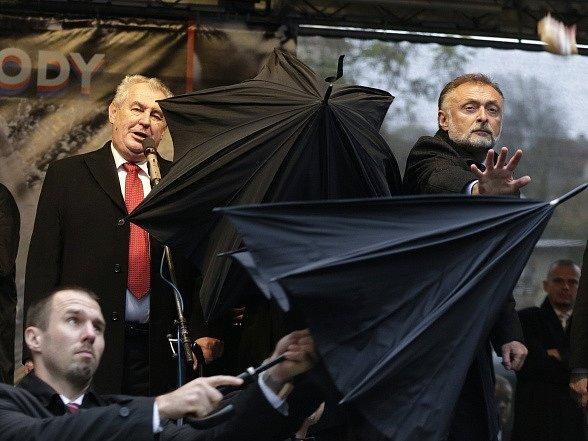 Ochranka chrání prezidenta Zemana před letícími předměty na pražském Albertově. 17. listopad 2014.