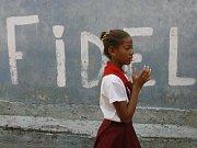 Pionýrka, která jde okolo nápisu viva Fidel v ulicích Havany.