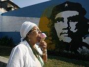 Žena, jež si vychutnává zmrzlinu na ulici v Havaně a prochází okolo nástěné malby Che Guevary