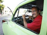 Muž kouřící doutník v okýnku svého vozu v Havaně