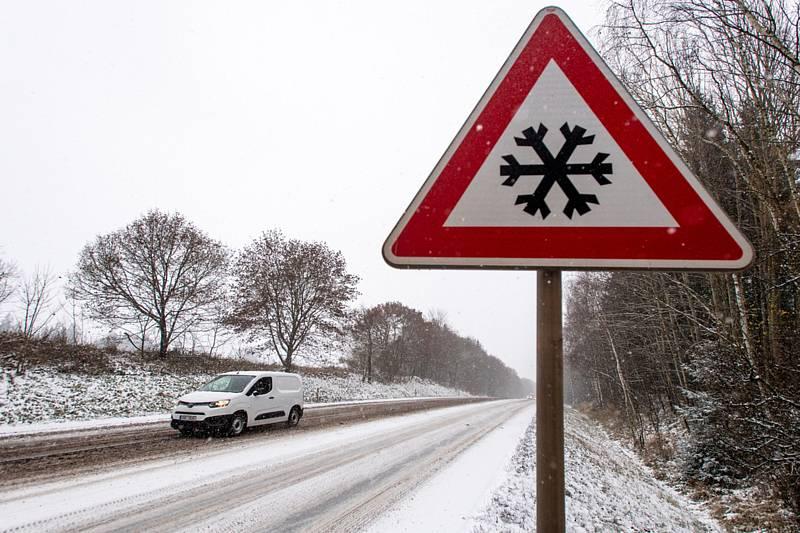 Automobil jede po zasněžené silnici