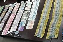 Nad číslem 15 jsou české tisícovky. Pod 13 jsou české stokoruny a pětistovky. Hotovost a platební karty zabavila pašerákům drog policie.