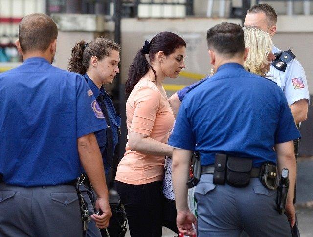 Jedna z obviněných Kateřina Pancová s eskortou vchází do budovy Krajského soudu v Praze, kde 7. srpna začíná hlavní líčení v kauze poslance a bývalého hejtmana Davida Ratha.