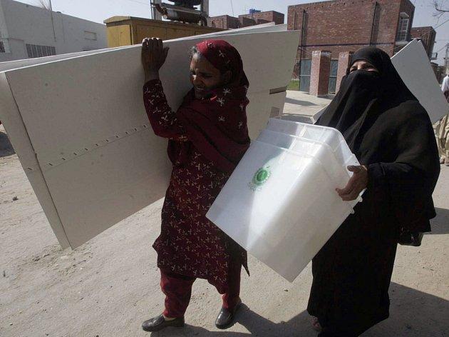 Členky volební komise nesou do volebních místností urny.