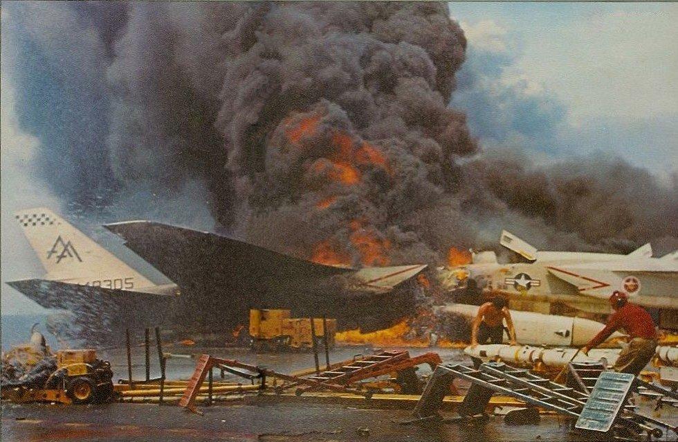 Záběr z hořící paluby letadlové lodi Forrestal, odkud se členové posádky snaží odnést rakety AGM-45 Shrike