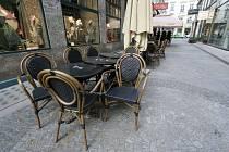 Prázdné stolky před kavárnou ve Vídni.