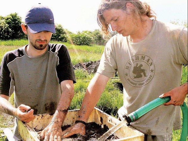 PROMÝVÁNÍ BAHNA. Studenti Západočeské univerzity v Plzni Jan Tauber (na snímku vlevo) a Miroslav Herian patří do týmu Petra Šídy. V bahně z vyhloubené jámy se snaží najít organické materiály.