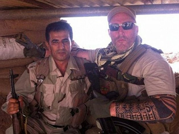 Motorkář Ron z gangu No Surrender pózuje s jedním z kurdských bojovníků.