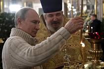 Ruský prezident Vladimir Putin zapalluje svíčky před vánoční bohoslužbou v moskevském chrámu Krista Spasitele