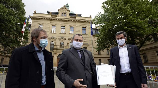 Zleva poslanec Petr Třešňák (Piráti), Jan Průha ze sdružení Pendleři bez hranic a senátor Miroslav Balatka (STAN) ukazují petici proti povinným testům na koronavirus, kterou předali vládě 5. května 2020 v Praze