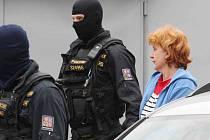 Policisté odvádějí obviněnou ženu do vazby.