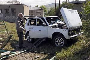 Muž si ve městě Stěpanakert v Ázerbájdžánu prohlíží svůj automobil zničený ostřelováním