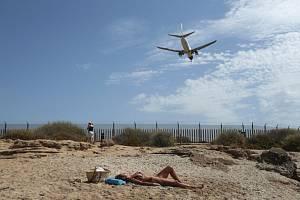 Žena se opaluje na pláži města Palma de Mallorca na španělských Baleárských ostrovech, nad pláží přelétá dopravní letoun chystající se k přistání (snímek z 29. července 2020)