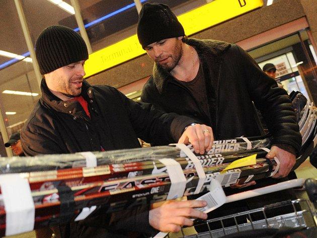Jakub Klepiš (vlevo) a Jaromír Jágr si rozdělují hokejky před letištní halou.