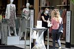 Pracovnice obchodu s oblečením pomáhá zákaznici s dezinfekcí rukou u vchodu do prodejny.