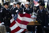 Památeční vlajka je přinášena na pódium během piety na památku obětí teroristických útoků 11. září 2001