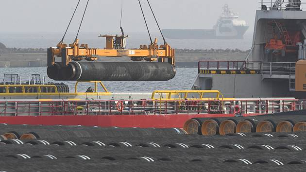 Jeřáb nakládá na loď potrubí pro plynovod Nord Stream 2 v baltském přístavu Mukran