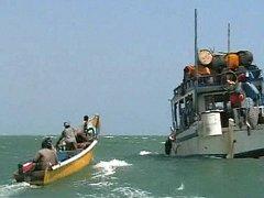 Piráti na člunu vedle svého mateřského plavidla u somálského přístavu Eyl.
