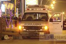 Tělo zavražděného policejního velitele ležící vedle sanitky, která ho převážela do nemocnice.