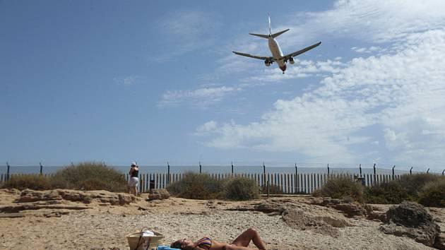 Žena se opaluje na pláži města Palma de Mallorca na španělských Baleárských ostrovech - Ilustrační foto