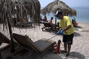 Dezinfikování lehátek na pláži v Řecku