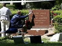 Policisté zajišťují stopy na rozbitém a vykradeném hrobě.