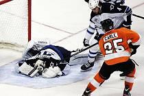 Brankář Winnipegu Ondřej Pavelec ukrývá puk před hráčem Philadelphie Mattem Carleem.