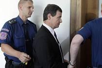 Policejní eskorta přivádí Davida Ratha k soudu.
