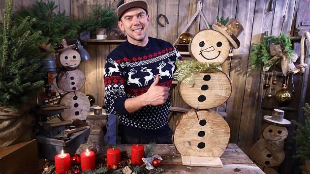 Láďa Hruška vyrábí sněhuláka z kulatiny.