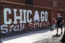 """Muž s dítětem v rouškách procházejí 12. dubna 2020 kolem povzbuzující zprávy """"Chicago zůstaň silné"""", kterou napsal křídou na zeď u chicagské hospody Roscoe Village umělec Heather Gentile Collins"""