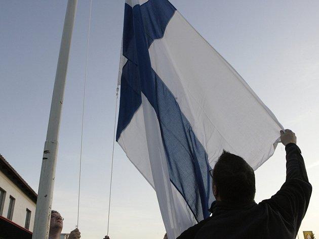 Obyvatelé spouštějí na půl žerdi finskou vlajku v Kauhajoki.