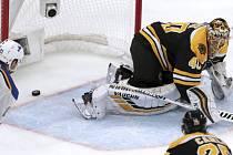 Střela z hokejky hráče St. Louis Blues Davida Perrona (není na snímku) končí za zády brankáře Bostonu Bruins Tuukka Raska (vpravo).