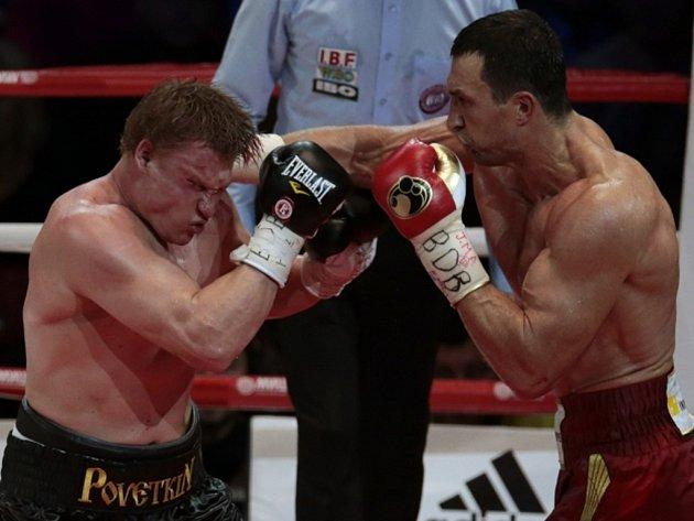 Vladimir Kličko (vpravo) zasazuje tvrdý úder Alexandru Povětkinovi v mistrovském zápase organizací WBO, IBF, IBO a WBA.