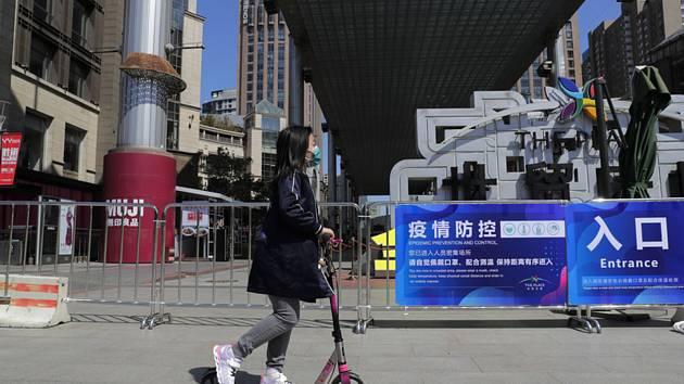 Dívka v roušce projíždí na koloběžce kolem uzavřeného nákupního centra v Pekingu, 20. dubna 2020