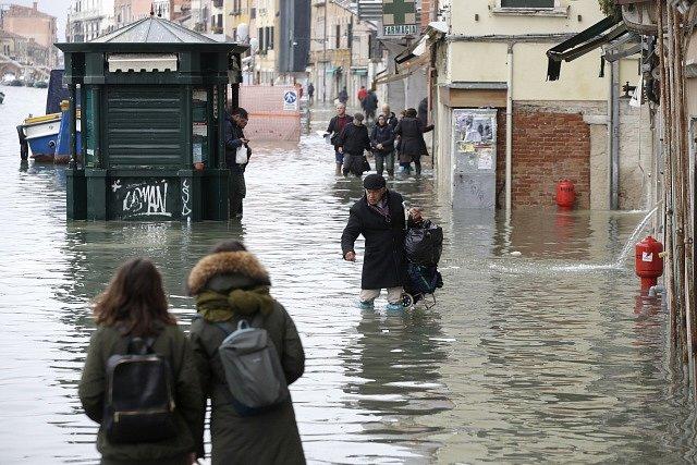 Nejhorší záplavy v Benátkách za 53 let. Lidé se na ulicich brodí ve vodě.