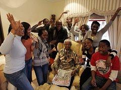Devadesátiletý jubilant obklopený svými vnuky.