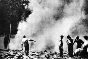 Členové sonderkommanda pálí v Osvětimi těla vězňů na venkovním ohništi poblíž krematoria V.