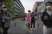 Lidé v rouškách v nákupní zóně v Pekingu, 24. dubna 2020