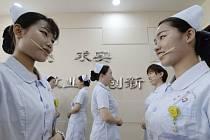 Čínské zdravotní sestry nacvičují správný zářivý úsměv