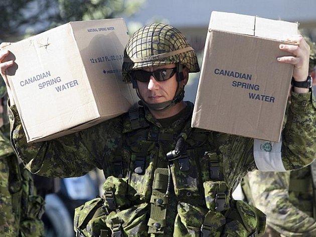 Kanadský voják nese bedy s vodou pro obyvatele Haiti. Na ostrov postižený zemetřesením sice proudí humanitární pomoc z celého světa, její distribuce je prý ale pomalá a vládne v ní zmatek.