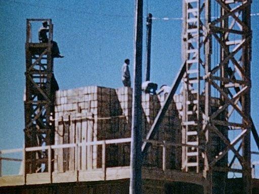 Muži skládají přepravky s výbušninami pro test stotunové jaderné bomby