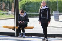 Dívky čekají 20. dubna 2020 na tramvaj před drážďanskou radnicí. Od téhož dne v Sasku platí kvůli koronaviru povinnost nosit ochranné roušky v obchodech a prostředcích veřejné dopravy