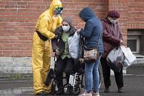 Zdravotníci pomáhají ženě na vozíku u nemocnice pro pacienty s nemocí covid-19 v Petrohradu, 18. května 2020