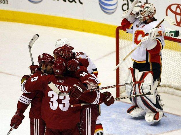 Hokejisté Phoenixu slaví vítěznou trefu Pyatta. V pozadí smutný gólman Calgary Miikka Kiprusoff.