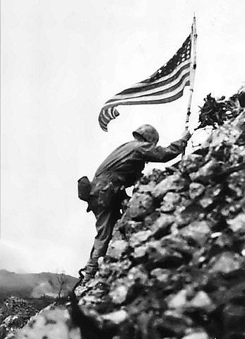 Velitel 3. praporu námořní pěchoty Richard P. Ross vztyčuje 30. května vlajku nad pevností ve městě Šuri ve středu ostrova