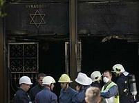 Hasiči stojí před ohořelou synagogou.