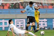 Jung-Woo Kim z Koreje (v bílém) vypichuje míč Suarézovi z Uruguaye.